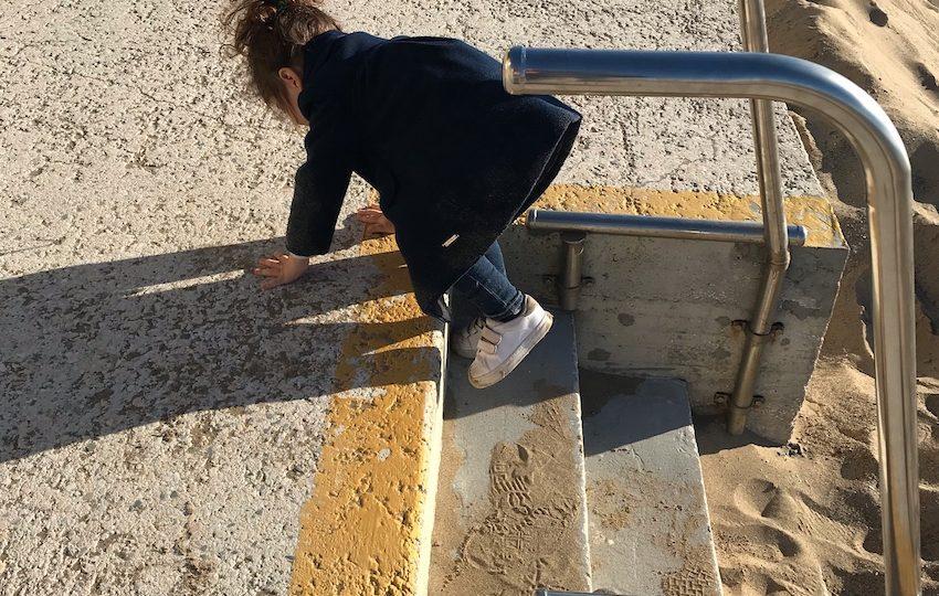 Rotolando nella sabbia, con cappotto e sneakers compresi